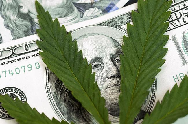 Feuille de cannabis sur les billets d'un dollar